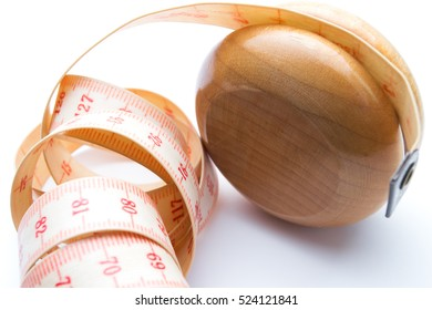 Yo-yo effect in diet concept. Wooden yoyo with centimeter measure. Closeup. Isolated on white background.