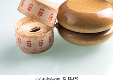 Yo-yo effect in diet concept. Wooden yoyo with centimeter measure. Reflective glass background.