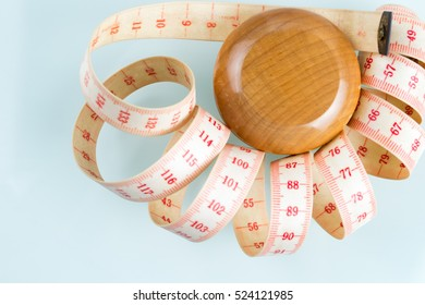Yo-yo effect in diet concept. Wooden yoyo with centimeter measure. Flat lay top view. Reflective glass background. Copy space in the bottom left corner.