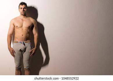 Ypoung strong male in night portrait shirtless looking at camera