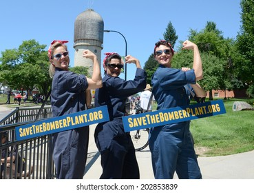 YPSILANTI, MI - JULY 4: Three women dressed as Rosie the Riveter advertise the campaign to preserve part of the Willow Run bomber plant after the 4th of July parade in Ypsilanti, MI July 4, 2014.