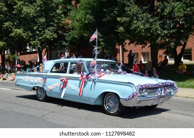 YPSILANTI, MI / USA - JULY 4, 2018:  A car decorated with 50 American flags as a tribute to veterans participates in the Ypsilanti Fourth of July parade.