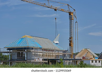 YSBRECHTUM, THE NETHERLANDS - JULY 4, 2018: An isolated prefab roofpart is hanging in the folding crane and will be placed on the roof of a new residential building. House surrounded by scaffolding.