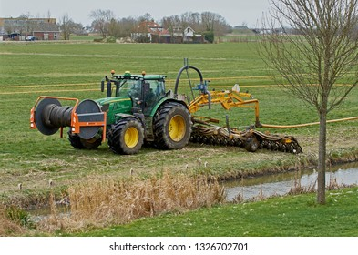 YSBRECHTUM, THE NETHERLANDS - MARCH 1, 2019: A John Deere tractor with a Tjalma slurry injection installation (in Dutch: sleepslang zode bemester) injecting liquid manure in a meadow. Low-emission.