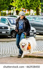 Ystad, Sweden - August 1, 2016: Real people in everyday life. Young adult man out walking with a Samoyed dog wearing an orange Ruffwear dog pack. Car park in background.