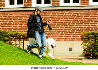 Ystad, Sweden - August 1, 2016: Real people in everyday life. Young adult man out walking with a Samoyed dog wearing an orange Ruffwear dog pack. Person has poo bag in hand.