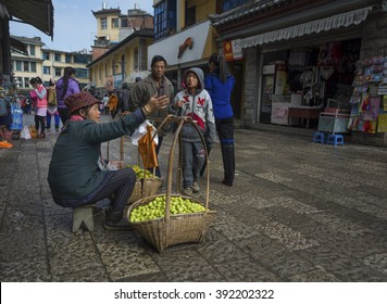 YUANYANG - March 01: Food stall vendors dressed in traditional costumes from the Yii ethnic minority wait for customers at their shop on March 01, 2016 in Yuan Yang County, China.