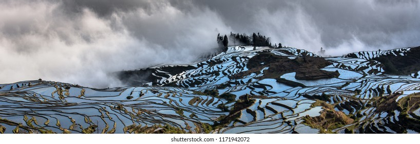 Yuanyang Rice Terraces in Yunnan Province, China - Early morning photograph with reflection of the sky causing water in the terraces to appear blue. Mist in the background, Duoyishu landscape, clouds