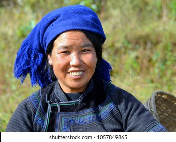 YUANYANG, YUNNAN / CHINA - NOV 15, 2012: Young Hani woman (Chinese ethnic minority) wears a black-and-blue traditional ethnic costume with blue headscarf and poses for the camera, on Nov 15, 2012.