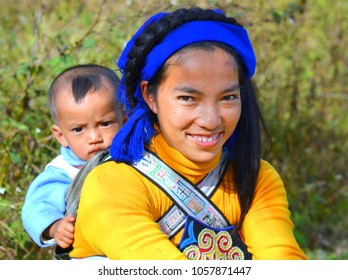 YUANYANG, YUNNAN / CHINA - NOV 15, 2012: Young Hani woman (Chinese ethnic minority) carries her baby boy in a traditional baby sling with ethnic design and poses for the camera, on Nov 15, 2012.