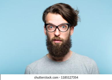 yuck. disgusted revolted bearded hipster guy wearing cat eye glasses. stylish modern fashionist. portrait of a geeky quirky eccentric man on blue background.