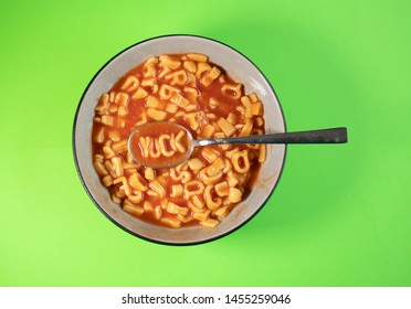 'YUCK' written with Alphabet Spaghetti on a spoon with e green background.
