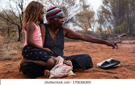Yuendumu, NT Australie, February 15 2020 : Aborigines Warlpiri in the bush. Family, grandmother and granddaughter, after hunting honey ants