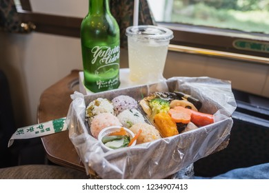 Yufuin,Oita,Kyushu,Japan - October 14, 2018 :Yufuin cider, special drink in Yufuin No Mori train, limited express train, route between Hakata station to Yufuin station, green bottle and bento sushi