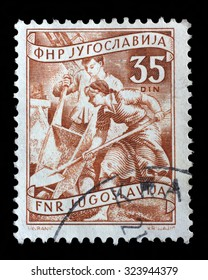 YUGOSLAVIA - CIRCA 1952: A stamp printed in Yugoslavia shows working at a construction site, domestic economy Series, stamp for surcharges, circa 1952