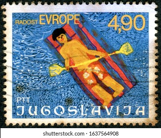 "YUGOSLAVIA - CIRCA 1977: A stamp printed in Yugoslavia, depicted ""Bathing"", children's drawing, circa 1977"
