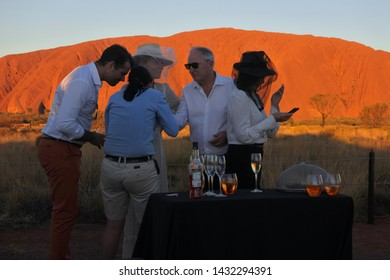 YULARA, NT - MAY 23 2019:Australian people drinking alcohol on Uluru Sunset Tour.Uluru is Australia's most natural icon and the focal point for Australia of Australian indigenous people
