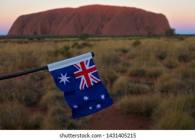 YULARA, NT - MAY 23 2019:Flag of Australia against Uluru (Ayers Rock) at sunset. Uluru is recognized as Australia's most natural icon and the focal point for Australia of Australian indigenous people.