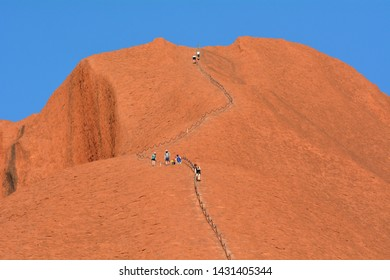YULARA, NT - MAY 23 2019:People climbing on Ayers Rock in Uluru-Kata Tjuta National Park.Uluru is Australia's most natural icon and the focal point for Australia of Australian indigenous people.