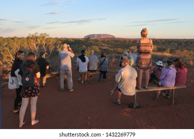 YULARA, NT - MAY 25 2019:Tourist looking at Uluru (Ayers Rock) during sunset. Uluru is Australia's most natural icon and the focal point for Australia of Australian indigenous people.