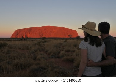 YULARA,NT-MAY 23 2019:Australian couple looking at Uluru (Ayers Rock) at sunset in Uluru-Kata Tjuta National Park.Uluru is Australia's most natural icon and focal point of Australian indigenous people