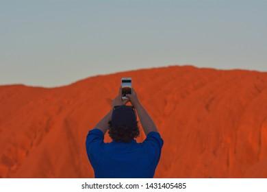 YULARA,NT-MAY 23 2019:Australian man photographing Uluru (Ayers Rock) at sunset in Uluru-Kata Tjuta National Park.Uluru is Australia's most natural icon and focal point of Australian indigenous people