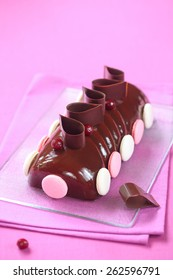 Yule Log Cake glazed with chocolate mirror glaze, decorated with chocolate loops, cherries and french macarons, on a transparent cutting board and bright pink background.