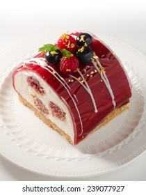 Yule log of white chocolate mousse, stuffed with raspberry puree sponge rolls, glazed with raspberry jelly, garnished with white chocolate, fresh berries, and gold leaf (also know as Buche de Noel)