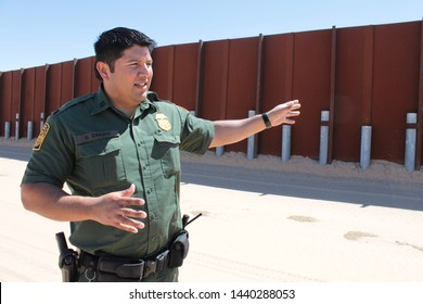 Yuma Sector, Ariz. / US - April 11, 2013: A Customs and Border Protection agent standing by a section of landing-mat fencing in the US-Mexico border wall. 1607