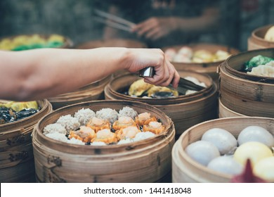 yumcha dim sum in bamboo steamer chinese cuisine hong kong. close up woman female hands holding tongs choosing meal different kinds delicious food in wood basket.