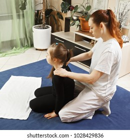 Yumeiho masseuse makes child shoulders massage sitting behind her. This oriental therapy is a complex set of manual procedures and physical exercises