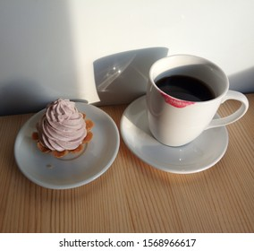 Yummy creamy cake and  fragrant coffee in the cup with red lipstick imprint on it on the wooden table