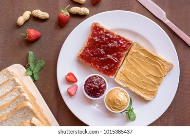 Yummy creamy peanut butter toast and strawberry jam toast on plate with nut and fruit. Diet food, Top view.
