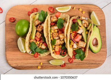 Yummy and crispy tacos with ingredients on a wooden cutting board. Mexican food and healthy eating, vegan lifestyle.