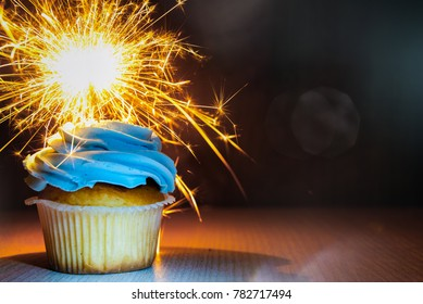 Yummy cupcake with buttercream and sparkler on wooden table against dark background with copy space.