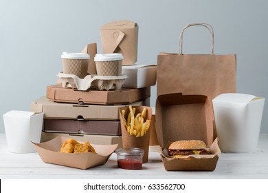 Yummy French fries, chicken Nuggets, hamburger, milkshake, sauce, latte and espresso. Pizza boxes and paper bag, light grey background. Binge eating.