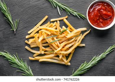 Yummy french fries on dark background