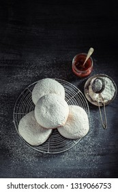 Yummy and fresh donuts on cooling grate on dark table