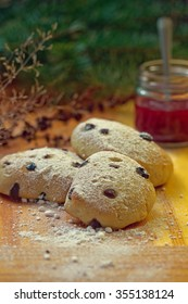 Yummy fresh homemade raisin buns decorated with sugar and jam jar in the background
