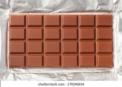 Yummy milk chocolate bar in open foil wrapping ready for eating. The foil is filled the frame of the image.
