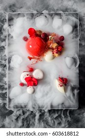 Yummy mousse cake, yogurt spheres, cherries, raspberries, a caramel decoration and fresh flowers in dry ice mist, a top-view image. Molecular food.