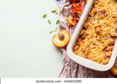 Yummy peach crumble dessert in baking pan on light background , top view. Copy space for your design or recipe