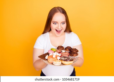Yummy! I'm a sweet-tooth! Portrait of excited cheerful with open mouth fatty lady looking at plate full of tasty delicious aromatic biscuits candies and cookies, isolated on bright yellow background