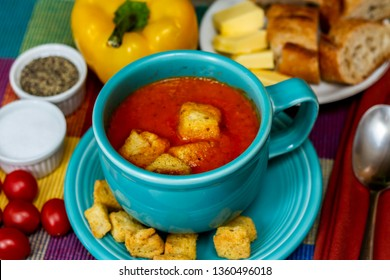 Yummy tomato and yellow pepper soup with croutons, tomatoes, salt, pepper and bread and butter. A nutritious lunch or dinner.