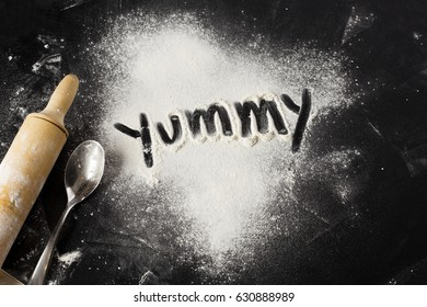 Yummy word written with flour on black table, rolling pin and spoon. Pastry recipe ingredients,