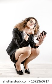 Yuna businesswoman squatting showing middle finger in phone and say Fuck you. emotional girl. Isolated on a gray background. Copy space