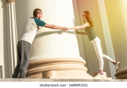 Yuna teenage couple walking around the historical architectural columns in a city park on a hot day. Love concept