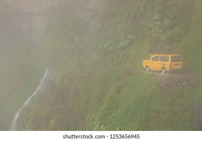 Yungas Road, Bolivia, February 2018: 'Death Road' due to its notoriously high death rate, was cut into the side of the Cordillera Oriental Mountain chain in the 1930s with dense fog and bus passing