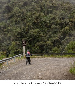 Yungas Road, Bolivia, February 2018: biker on the 'Death Road' due to its notoriously high death rate, was cut into the side of the Cordillera Oriental Mountain chain in the 1930s.