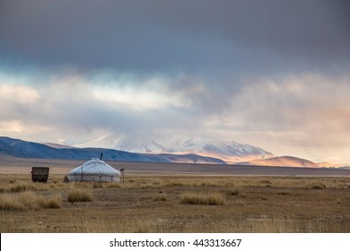Yurt in Mongolian landscape with snowy mountains at the background